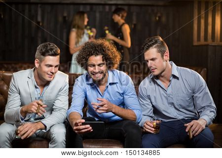 Three happy friends looking at mobile phone while having cigar and whisky in bar