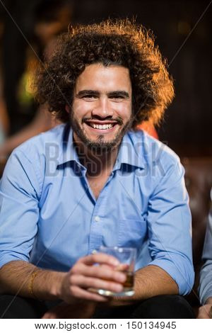 Portrait of smiling man holding glass of whisky in bar