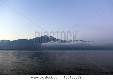 Beautiful view by a misty morning at sunrise on Lake Geneva, a surreal impression as the alps emerge in the distance in Montreux, Switzerland