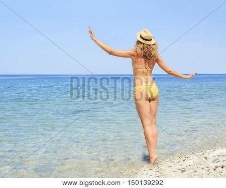 Lovely young woman in a bikini enjoying the ocean breezes