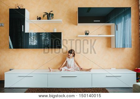 little girl sitting on twine (split) on furniture