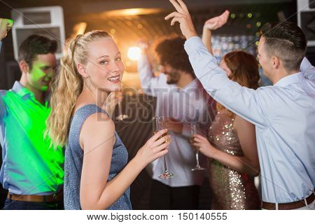 Portrait of smiling woman holding glass of champagne while dancing with friends at bar