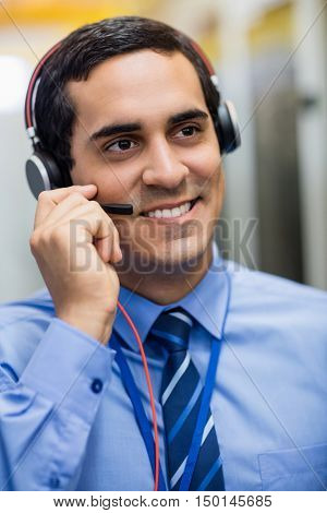 Close-up of happy technician talking on head phones