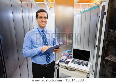 Portrait of happy technician holding clipboard in server room