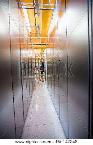 Technician working in hallway of server room