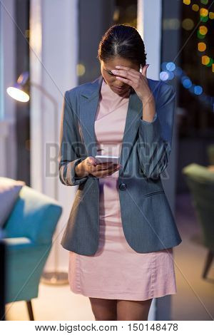 Tensed businesswoman using mobile phone in office at night