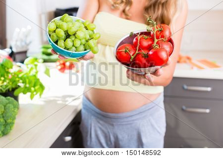 Pregnant woman showing fruit and vegetables - tomatoes and grapes