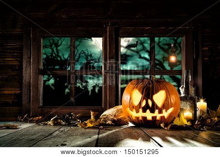 Scary halloween pumpkin on wooden planks, placed in front of window with scary background