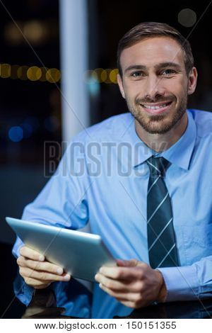 Portrait of happy businessman using digital tablet in office at night