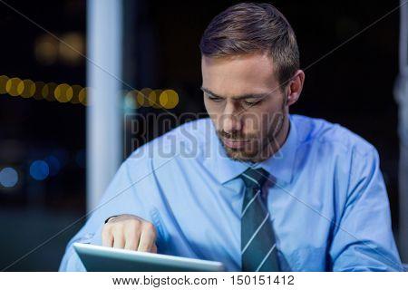 Attentive businessman using digital tablet in office at night