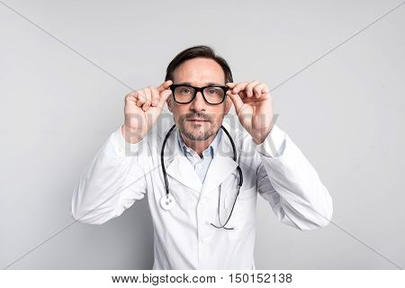 Oh my God. Handsome young doctor staring and touching his glasses while standing against grey background.
