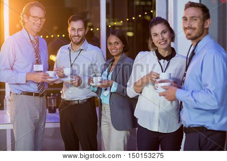 Group of businesspeople having coffee during break in office at night