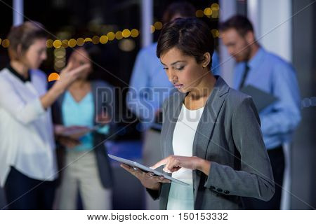 Businesswoman using digital tablet in office at night