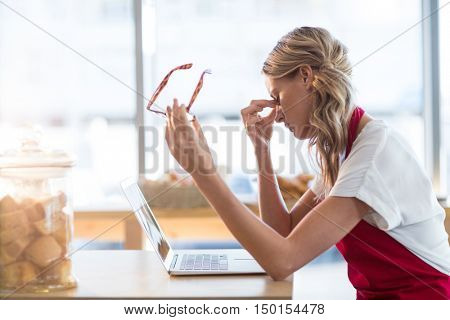 Tired waitress sitting at table and using laptop in caf\x92\xA9