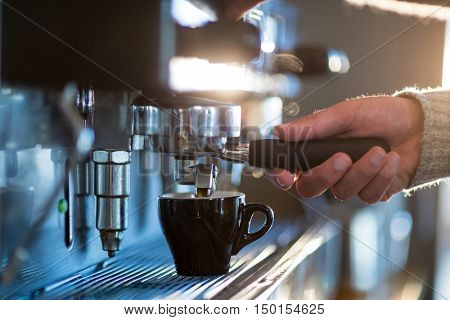 Waiter making cup of coffee at counter in kitchen at caf\x92\xA9
