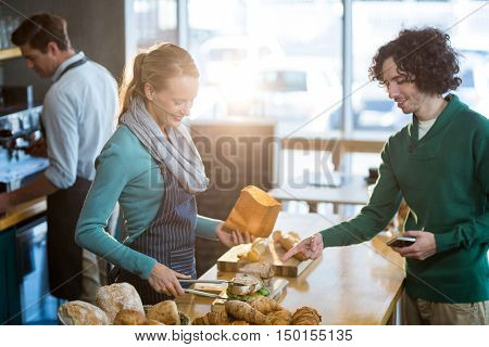Female waitress packing sandwich in paper bag at caf\x92\xA9