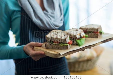 Mid-section of waitress holding a tray with sandwiches in caf\x92\xA9