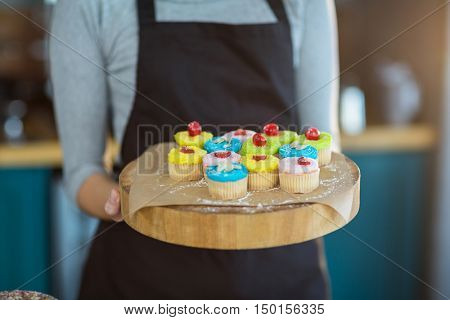 Mid-section of waitress holding cup cake on tray in caf\x92\xA9