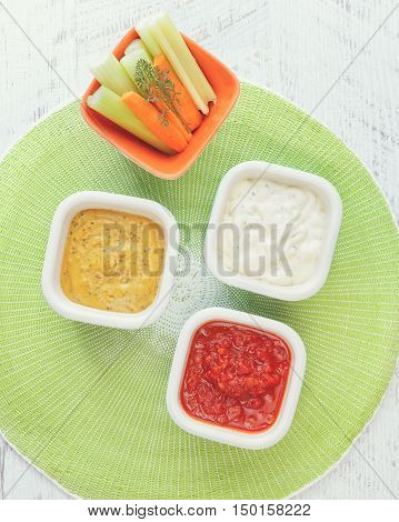 Crudites with dip. Dishes of various vegetarian dips, top view, blank space
