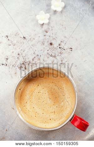 coffee in unusual vintage tin mug with red handle on old tin backdrop