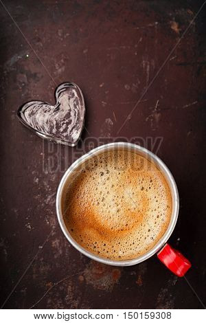 coffee in unusual vintage tin mug with red handle on old metal backdrop with glass heart