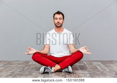 Man in casual cloth sitting in lotus position over gray background