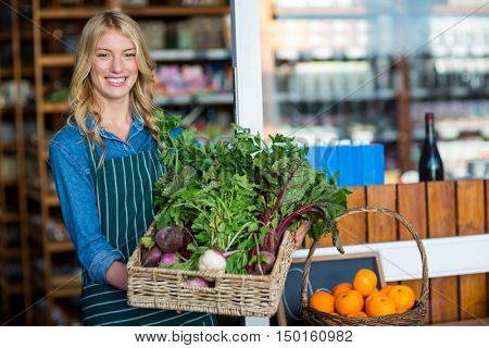 Portrait of a smiling staff holding a basket of fresh vegetables in organic section of supermarket