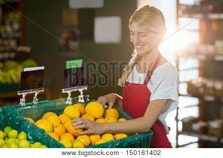 Smiling female staff checking fruits in organic section of supermarket