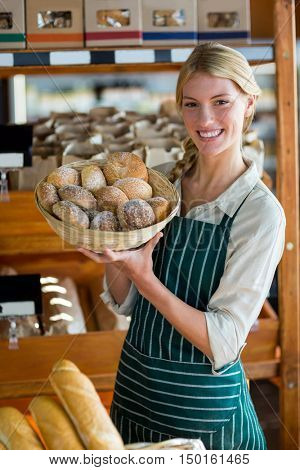 Portrait of smiling female staff holding basket of sesame breads at bread counter in supermarket