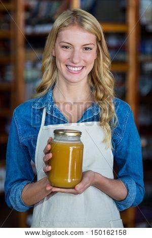 Portrait of smiling female staff holding jar of honey in supermarket