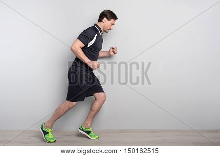 Ready steady go. Handsome serious man running on grey background while expressing confidence