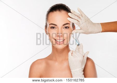 Beautiful young woman gets beauty injection in eye area from sergeant isolated on white background