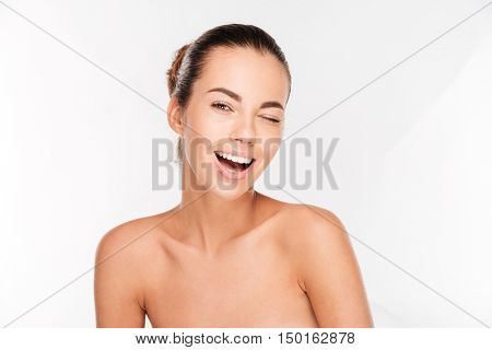 Beauty portrait of a young woman with fresh skin winking isolated on a white background