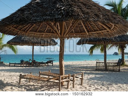 beautiful clean Zanzibar beach with thatched handmade umbrellas and wooden benches
