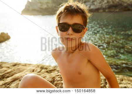 Happy boy enjoys summer holidays at the seaside. Happy childhood.