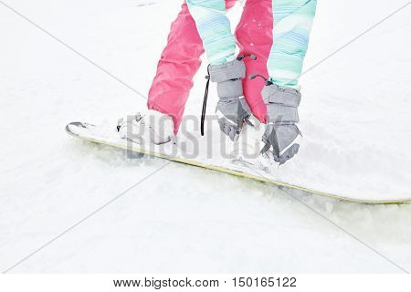 Close up of female snowboarder wearing grey gloves, pink pants and white boots adjusting bindings on her snowboard - snowboarding and winter sports concept
