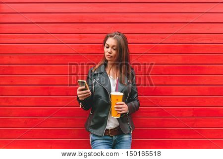 girl using mobile phone, writing SMS, with a drink in his hand on a red wooden wall