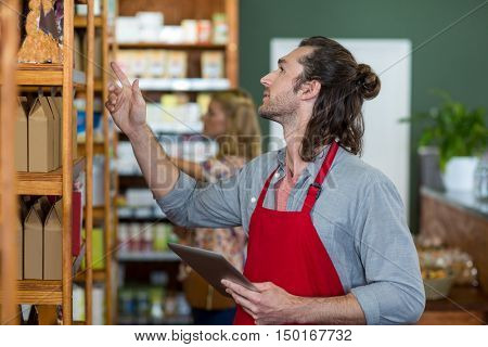 Male staff holding a digital tablet and checking grocery products on the shelf in supermarket
