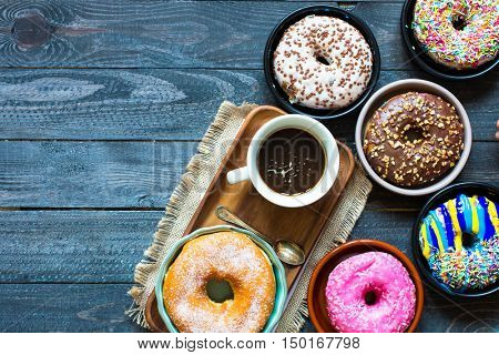 Colorful Donuts breakfast composition with different color styles of doughnuts and fresh coffee on the side over an aged wooden desk background.