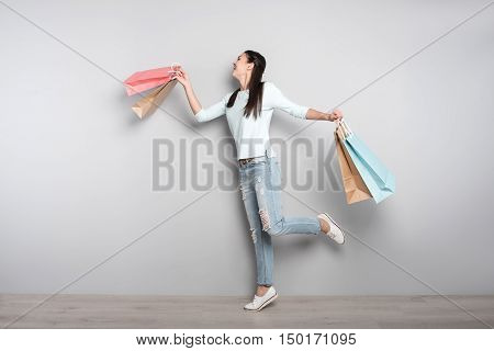 High spirit. Positive content young woman holding packages and walking while resting after shopping