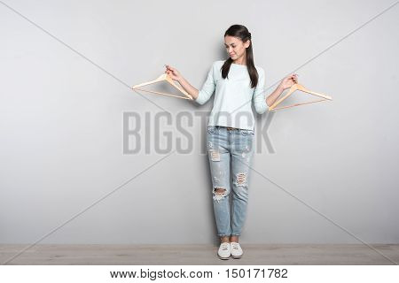 What to choose. Pleasant beautiful woman holding clothes hangers and choosing what to wear while standing against grey background