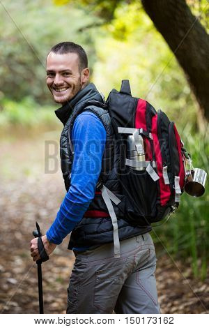 Portrait of smiling male hiker walking with hiking pole in forest