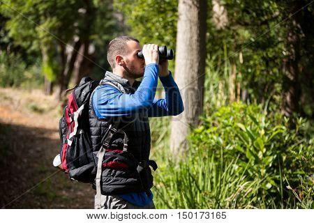 Male hiker looking through binoculars in forest