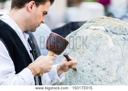 Sculptor with mallet and cutter working on erratic block
