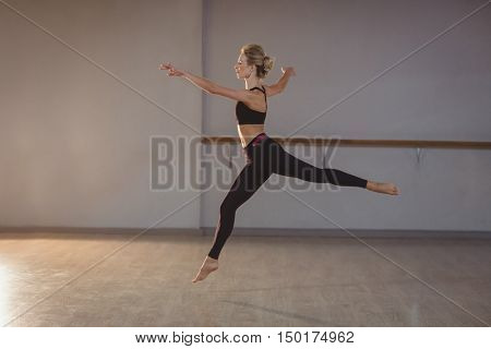 Woman leaping while performing stretching exercise in fitness studio