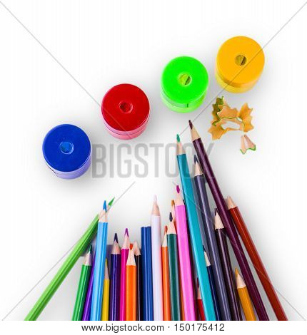 some colored pencils of different colors and a pencil sharpeners and pencil shavings on a white background