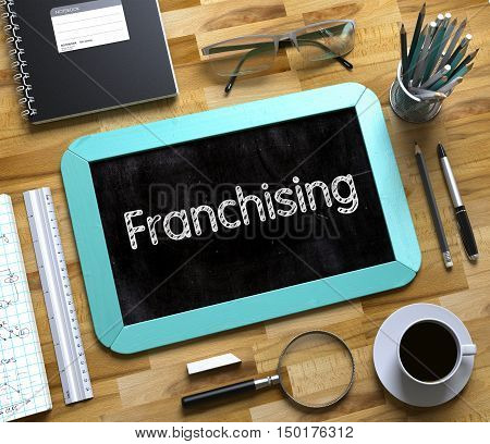 Franchising on Small Chalkboard. Franchising Handwritten on Mint Small Chalkboard. Top View of Wooden Office Desk with a Lot of Business and Office Supplies on It. 3d Rendering.