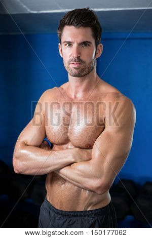 Portrait of male athlete with arms crossed while standing in gym