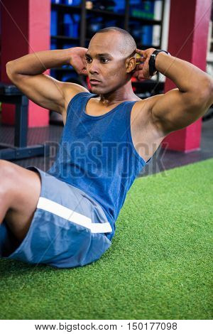 Serious young athlete exercising in gym