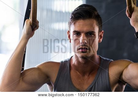 Portrait of young man using gymnastic rings while exercising in gym